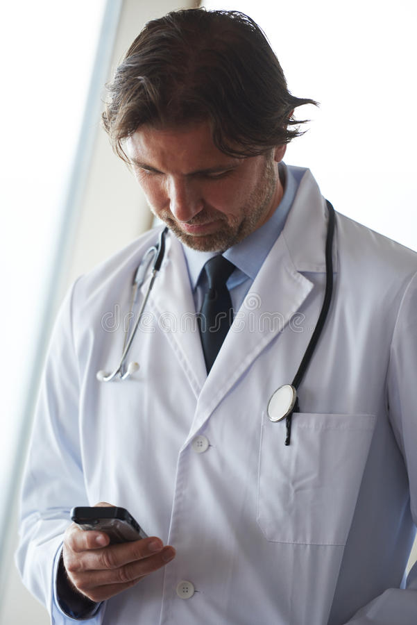 Doctor speaking on cellphone. Handsome doctor speaking on cellphone at modern hospital indoors royalty free stock photo
