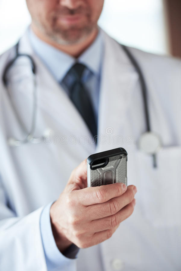Doctor speaking on cellphone. Handsome doctor speaking on cellphone at modern hospital indoors stock photography