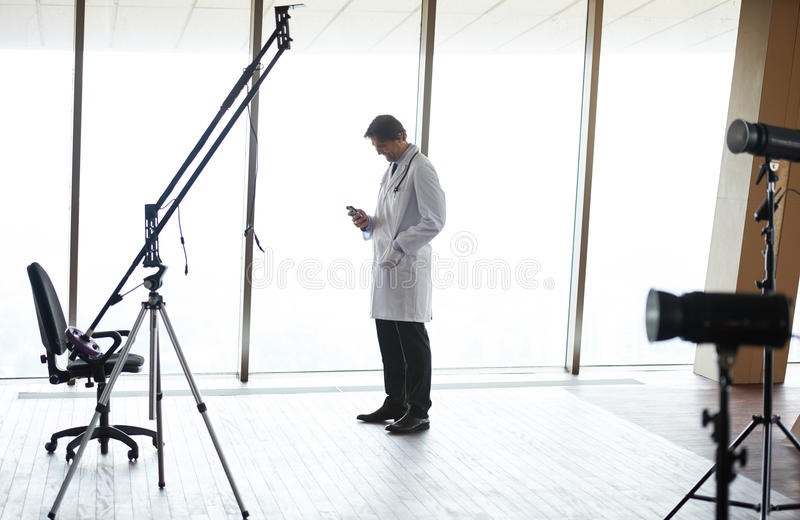Doctor speaking on cellphone. Handsome doctor speaking on cellphone at modern hospital indoors royalty free stock image