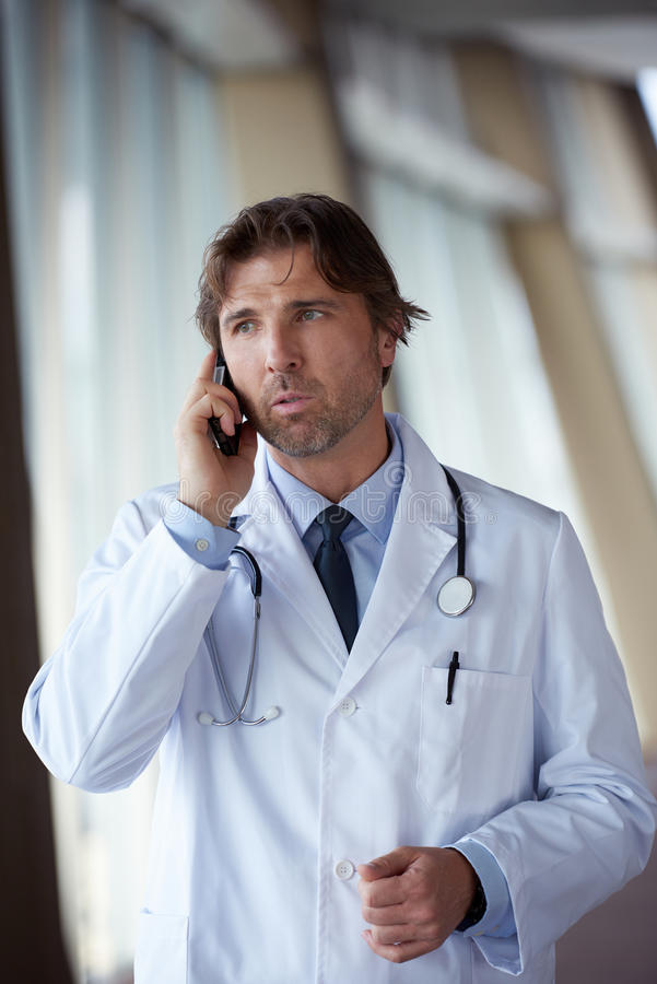 Doctor speaking on cellphone. Handsome doctor speaking on cellphone at modern hospital indoors royalty free stock photography