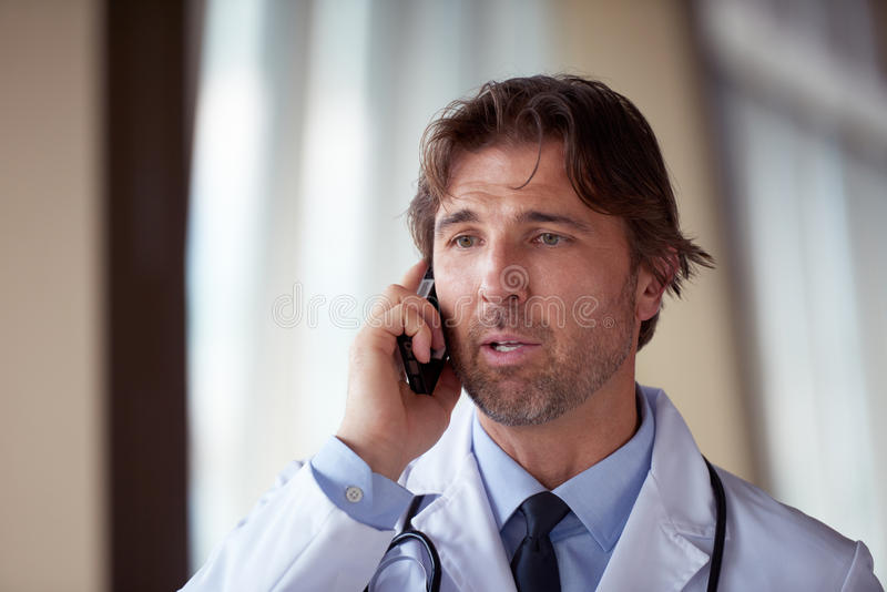 Doctor speaking on cellphone. Handsome doctor speaking on cellphone at modern hospital indoors stock photos