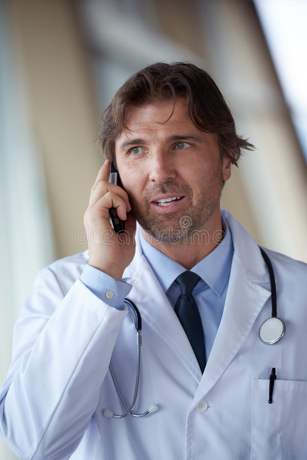 Doctor speaking on cellphone. Handsome doctor speaking on cellphone at modern hospital indoors royalty free stock photos