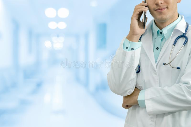 Doctor Speaking on Phone. Male doctor speaking on mobile phone in a hospital or doctors office. Concept of call center, medical consulting by doctor royalty free stock photos