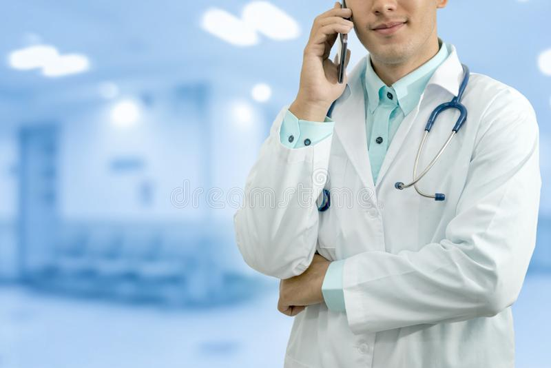 Doctor Speaking on Phone. Male doctor speaking on mobile phone in a hospital or doctors office. Concept of call center, medical consulting by doctor royalty free stock images