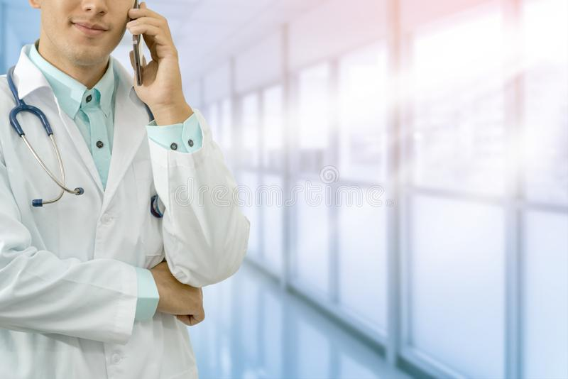 Doctor Speaking on Phone. Male doctor speaking on mobile phone in a hospital or doctors office. Concept of call center, medical consulting by doctor stock images