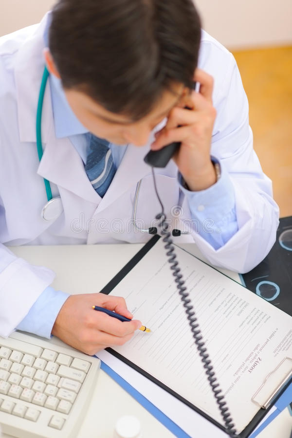 Doctor speaking phone and notes in clipboardyo. Medical doctor speaking phone and notes in clipboard. Top view stock photo