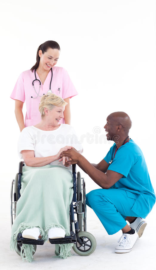 Doctor speaking to a patient in a wheel chair. Afro-American doctor speaking to a senior patient in a wheel chair royalty free stock photo