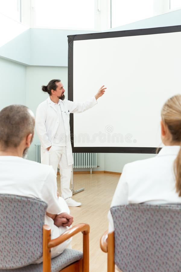 Doctor is standing in front of a empty whiteboard. Giving a lecture or briefing stock images