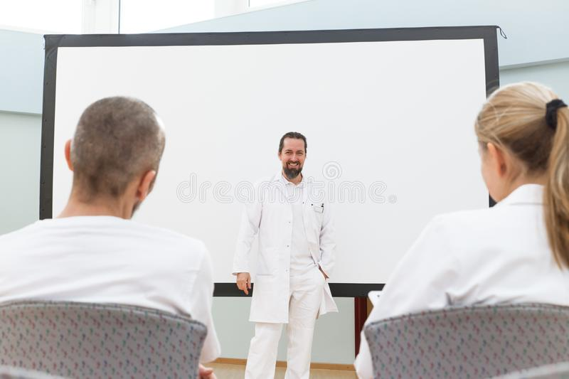 Doctor is standing in front of a empty whiteboard. Giving a lecture or briefing royalty free stock photography