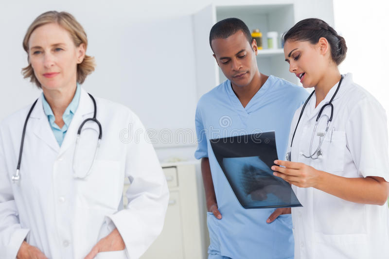 Doctor standing in front of medical team stock photo
