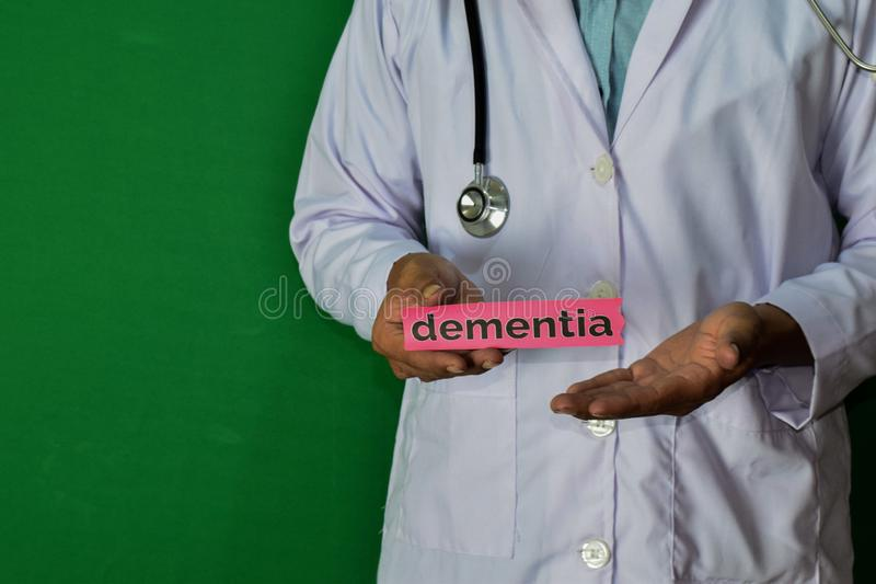 Doctor standing on Green background. Hold the Dementia paper text. Medical and healthcare concept royalty free stock photos