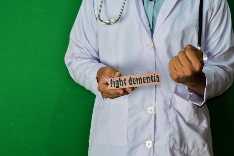 Doctor standing on Green background. Hold the Fight Dementia paper text. royalty free stock photo