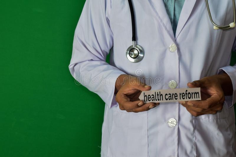 Doctor standing on Green background. Hold the Health Care Reform paper text. Medical and healthcare concept stock photography