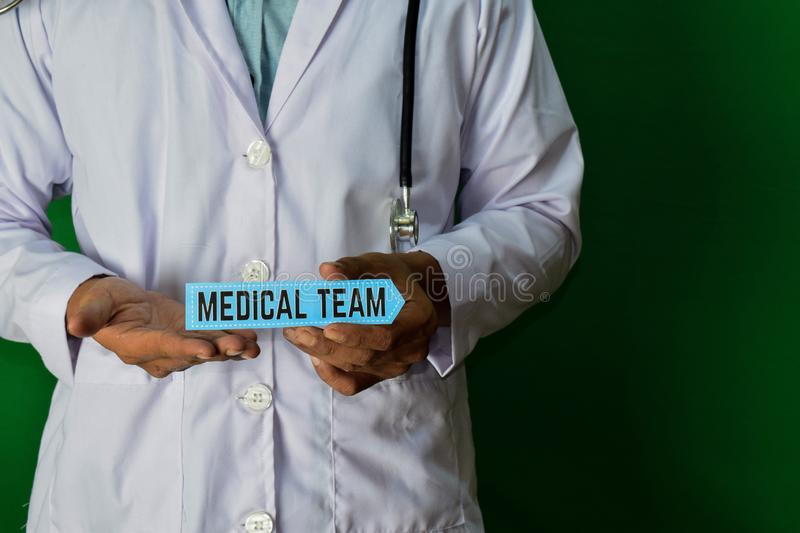 Doctor standing on Green background. Hold the Medical Team paper text royalty free stock image