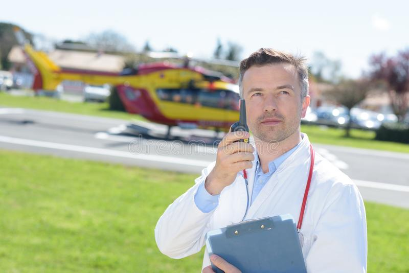 Doctor standing by helicopter with walkie-talkie. Doctor standing by a helicopter with walkie-talkie royalty free stock images