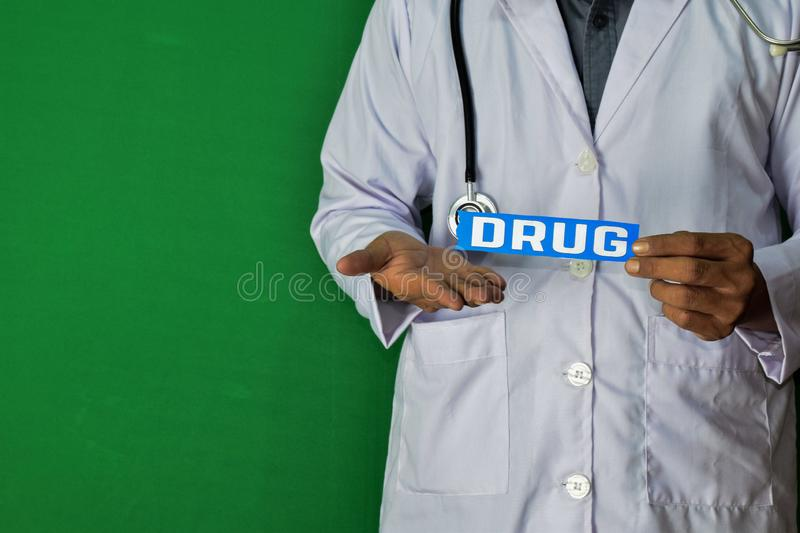 A doctor standing, Hold the Drug paper text on Green background. Medical and healthcare concept stock images