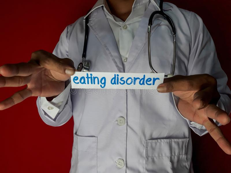 A doctor standing, Hold the eating disorder paper text on red background. Medical and healthcare concept stock photos