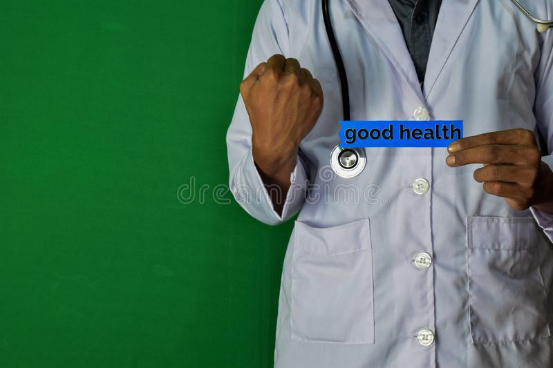 A doctor standing, Hold the Good Health paper text on Green background. Medical and healthcare concept royalty free stock images