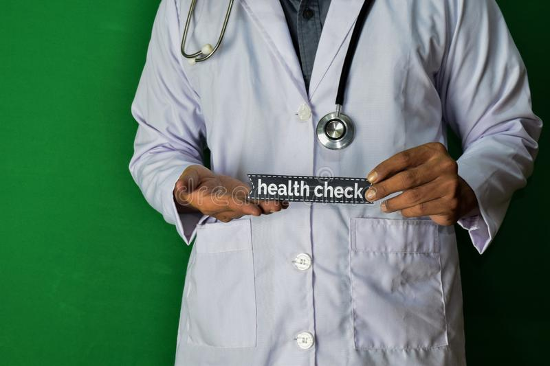 A doctor standing, Hold the Health Check paper text on Green background. Medical and healthcare concept royalty free stock photo