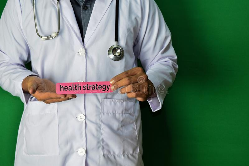 A doctor standing, Hold the Health Strategy paper text on Green background. Medical and healthcare concept stock photography