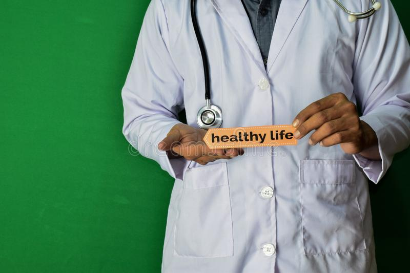 A doctor standing, Hold the Healthy Life paper text on Green background. Medical and healthcare concept stock image