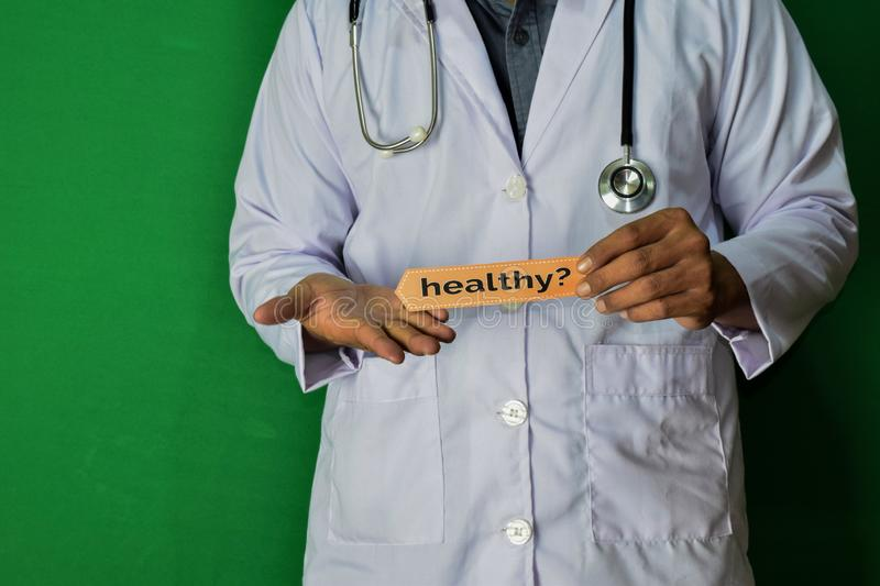 A doctor standing, Hold the Healthy? paper text on Green background. Medical and healthcare concept stock photo