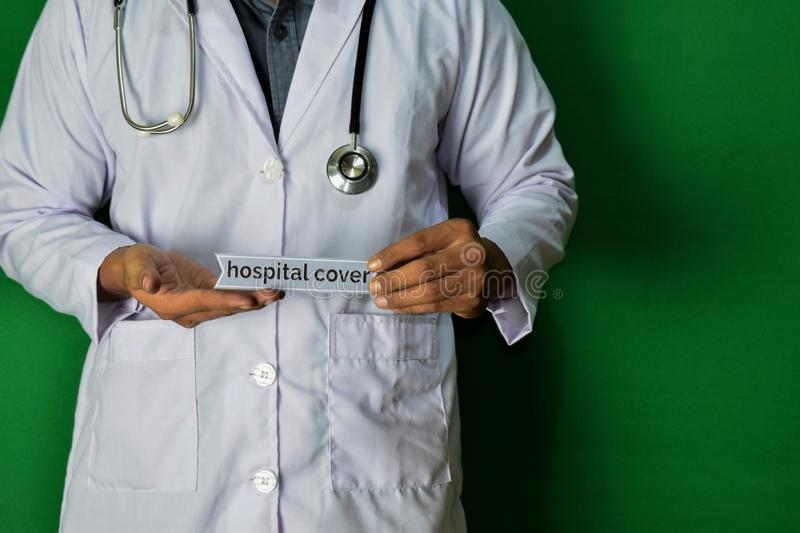 A doctor standing, Hold the Hospital Cover paper text on Green background. Medical and healthcare concept royalty free stock photos