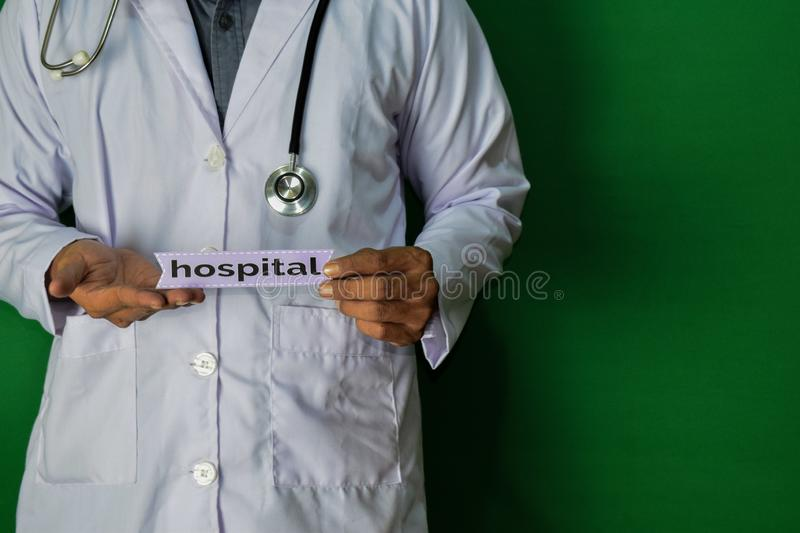 A doctor standing, Hold the Hospital paper text on Green background. Medical and healthcare concept stock photography
