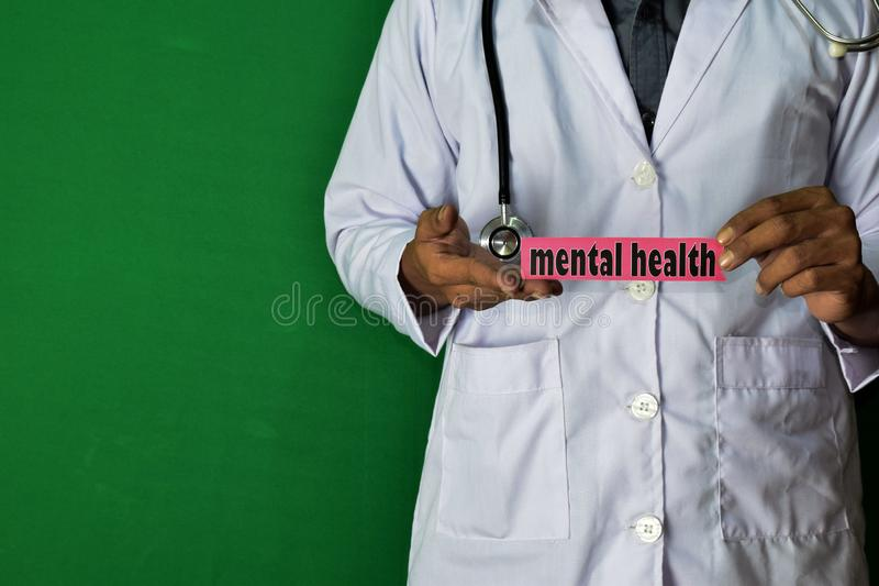 A doctor standing, Hold the Mental Health paper text on Green background. Medical and healthcare concept stock image