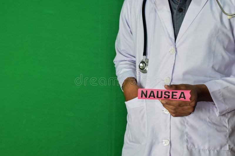 A doctor standing, Hold the Nausea paper text on Green background. Medical and healthcare concept stock photos