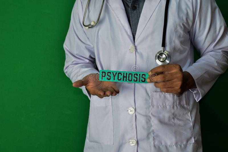 A doctor standing, Hold the Psychosis paper text on Green background. Medical and healthcare concept royalty free stock photo