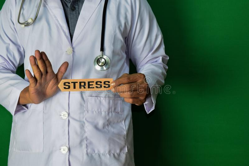 A doctor standing, Hold the Stress paper text on Green background. Medical and healthcare concept stock images