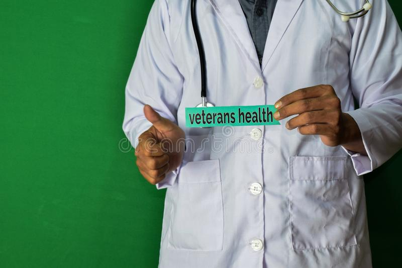 A doctor standing, Hold the Veterans Health paper text on Green background. Medical and healthcare concept stock photo
