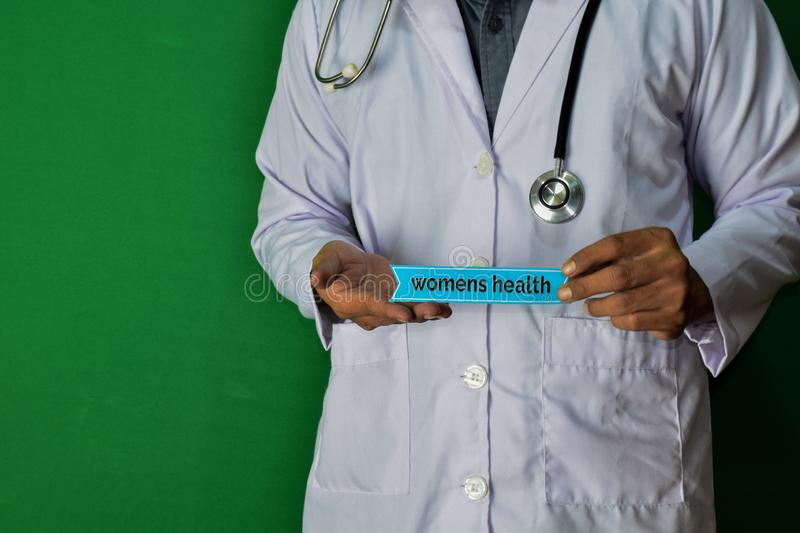 A doctor standing, Hold the Womens Health paper text on Green background. Medical and healthcare concept stock photography