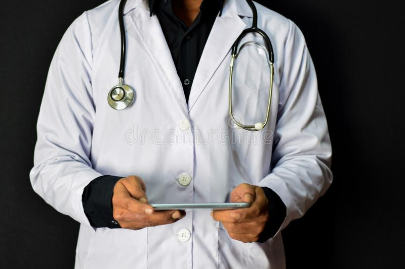 Doctor standing holding smartphone on black background. Medical and healthcare concept royalty free stock image