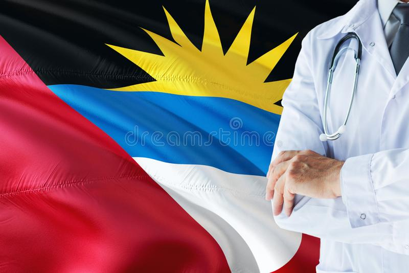 Doctor standing with stethoscope on Antigua and Barbuda flag background. National healthcare system concept, medical theme stock photos