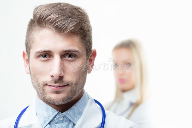 Doctor with stethoscope around his neck smiling at the camera stock images