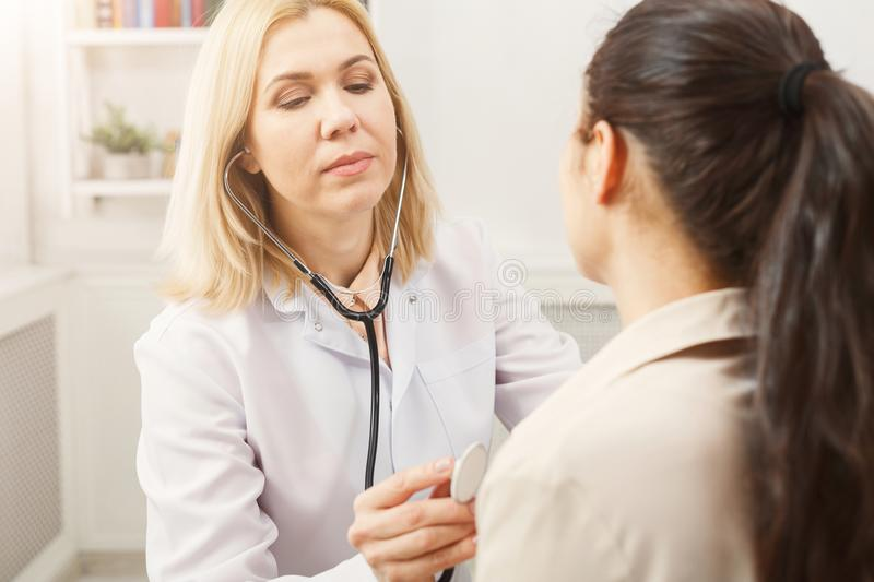 Doctor with stethoscope checking patient heart beat royalty free stock images