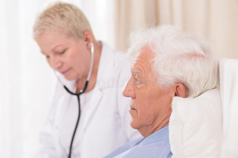 Doctor with stethoscope examining patient. Close up of female doctor with stethoscope examining senior patient royalty free stock images
