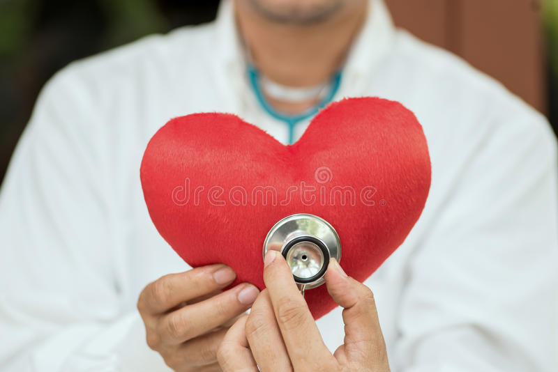 A doctor with stethoscope examining a red heart. Background blood cardiologist cardiology check closeup coat concept diagnosis doctor doctors equipment exam royalty free stock photo
