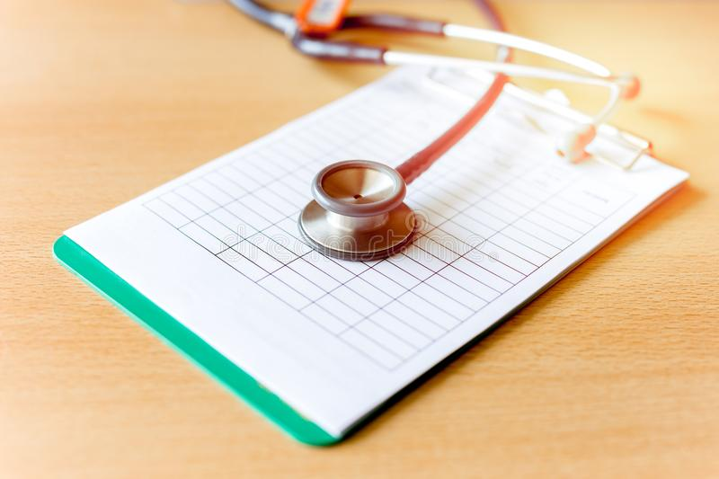 Doctor stethoscope head on medical forms. On wooden table royalty free stock images