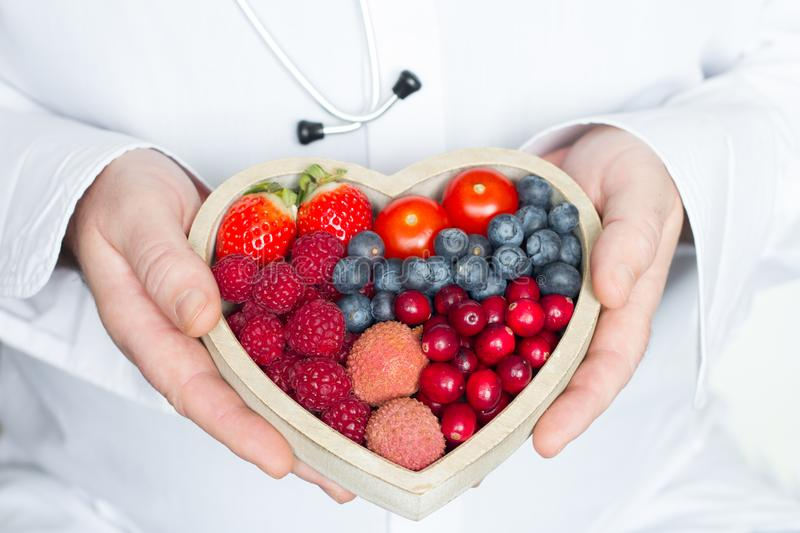 Doctor and stethoscope with heart healthy diet food abstract medicine concept. Closeup stock image