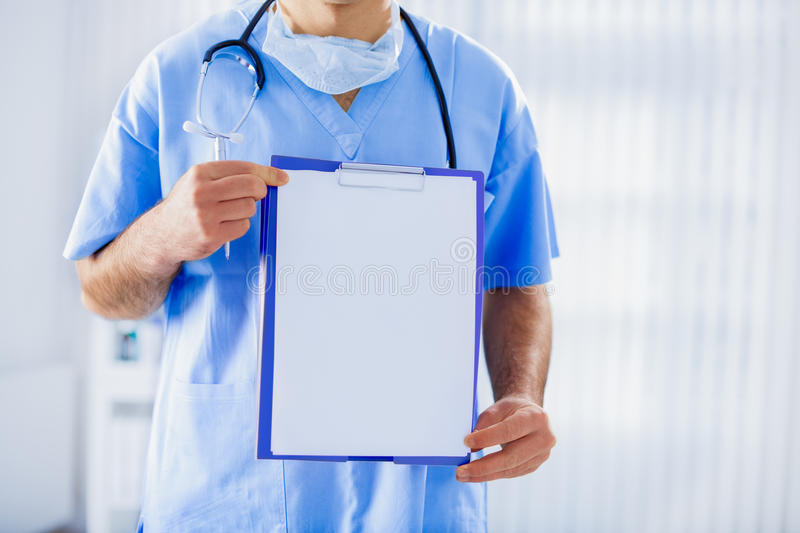 Doctor with stethoscope and medical card stock photo