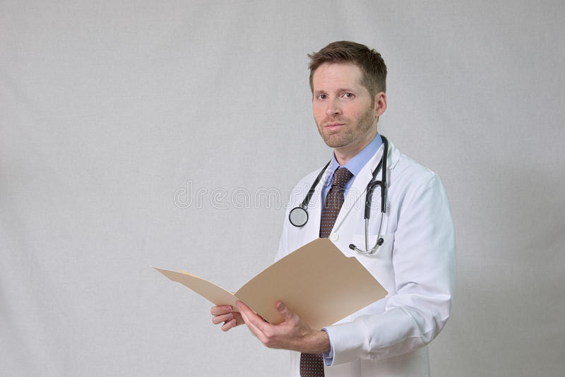 Doctor with Stethoscope and Patient Chart. Half length, 3/4 portrait of friendly doctor isolated on white background in studio. Subject is wearing a white coat royalty free stock photos