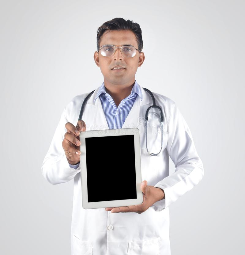 Doctor with stethoscope showing blank tablet pc screen stock images