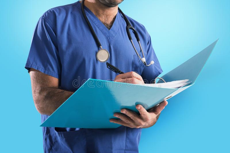 Doctor with stethoscope writes on medical record. On blue background stock photo