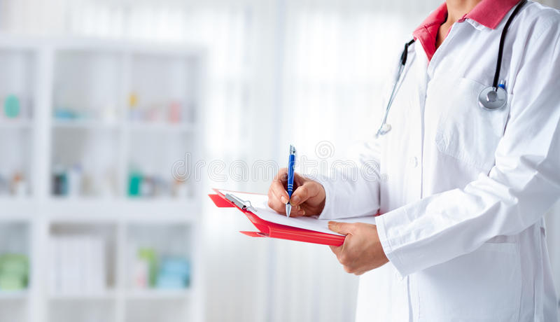 Doctor with stethoscope writing on a hospital cardboard stock photography