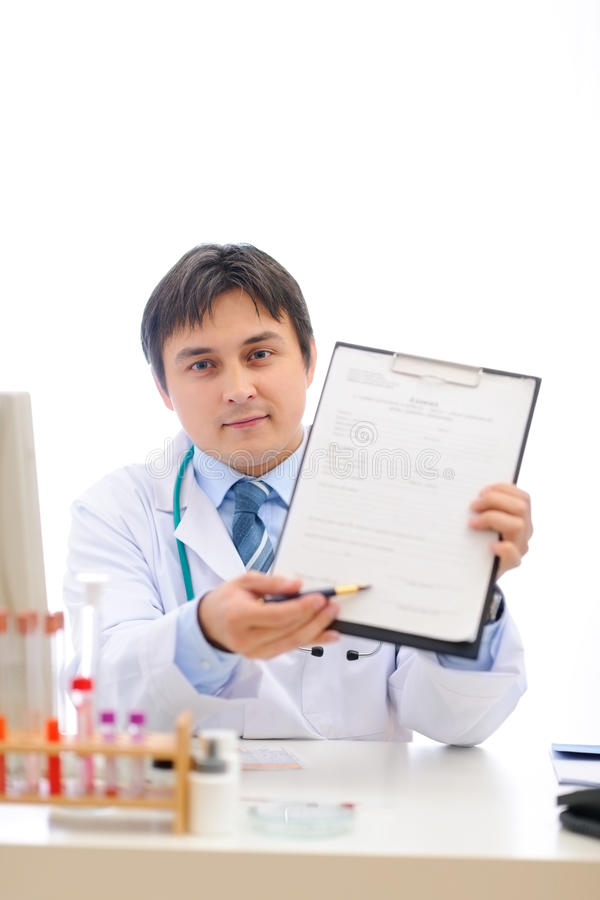 Doctor stretching clipboard for you to sign royalty free stock images