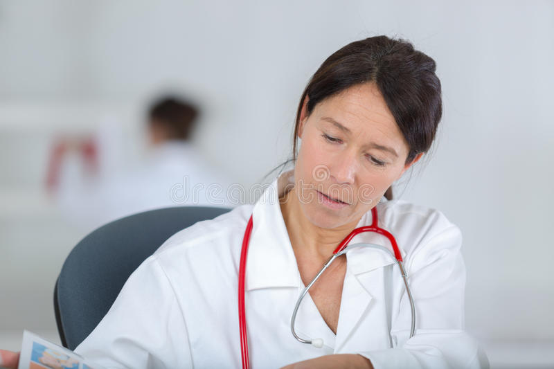 Doctor subrayado de la mujer que se sienta en oficina imagen de archivo libre de regalías