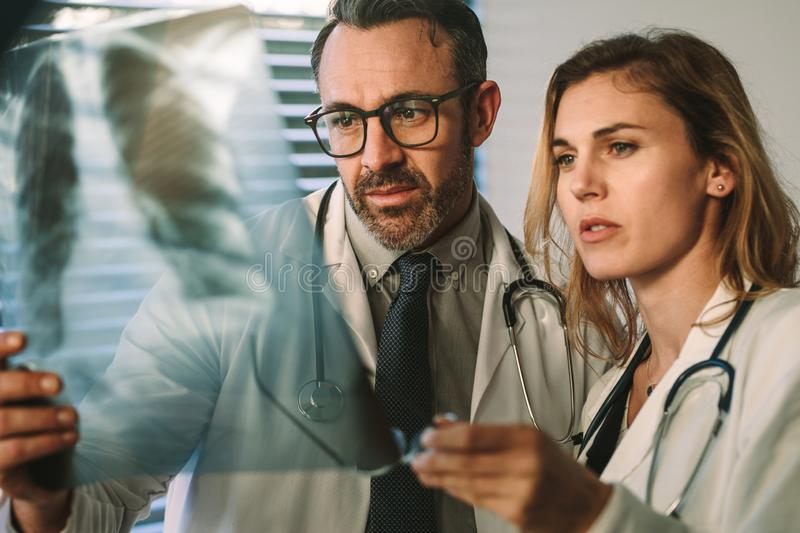 Doctor and surgeon closely studying x-ray of patient royalty free stock photo
